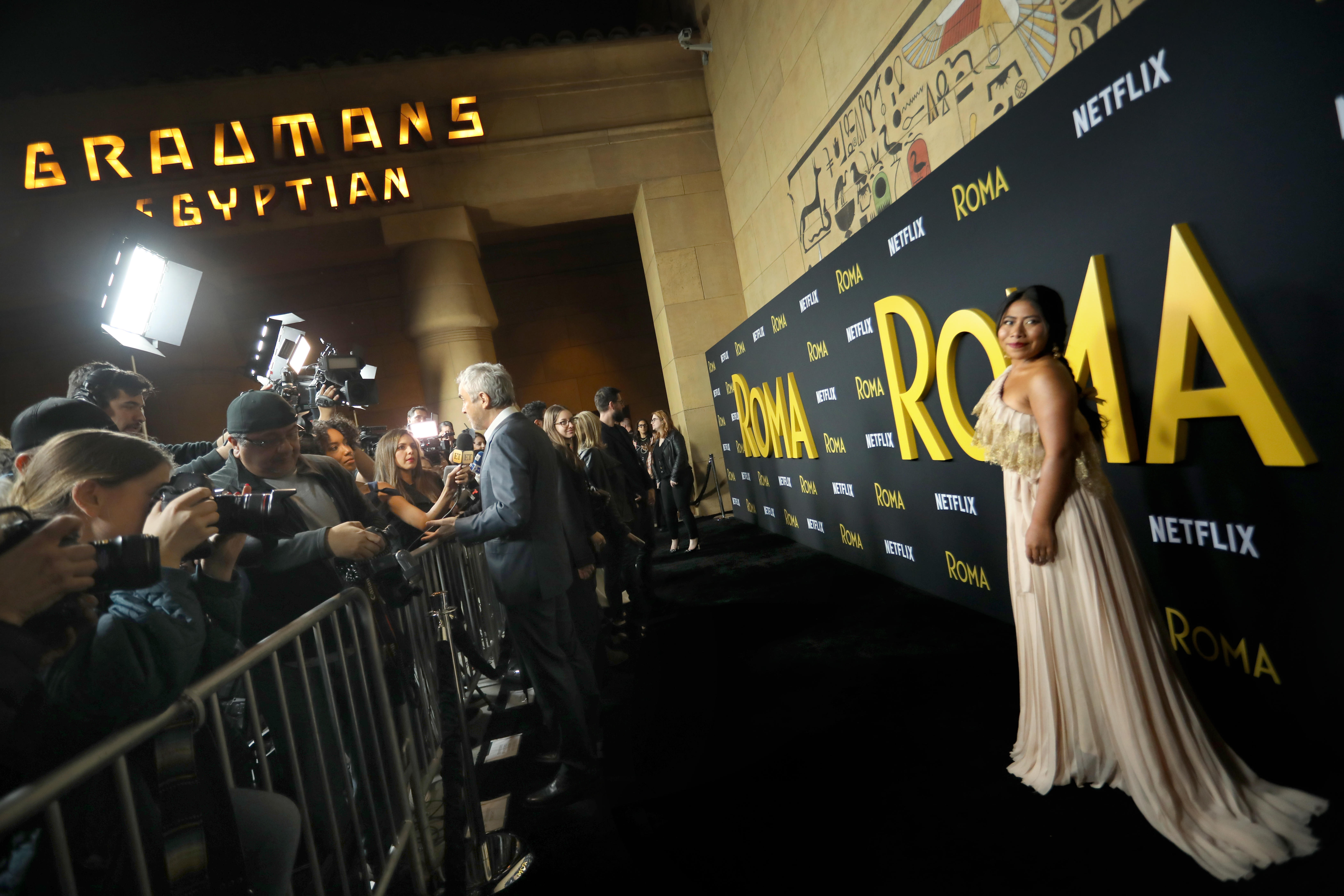 Actress Yalitza Aparicio poses for flashing cameras on the red carpet in courtyard of the Egyptian theater
