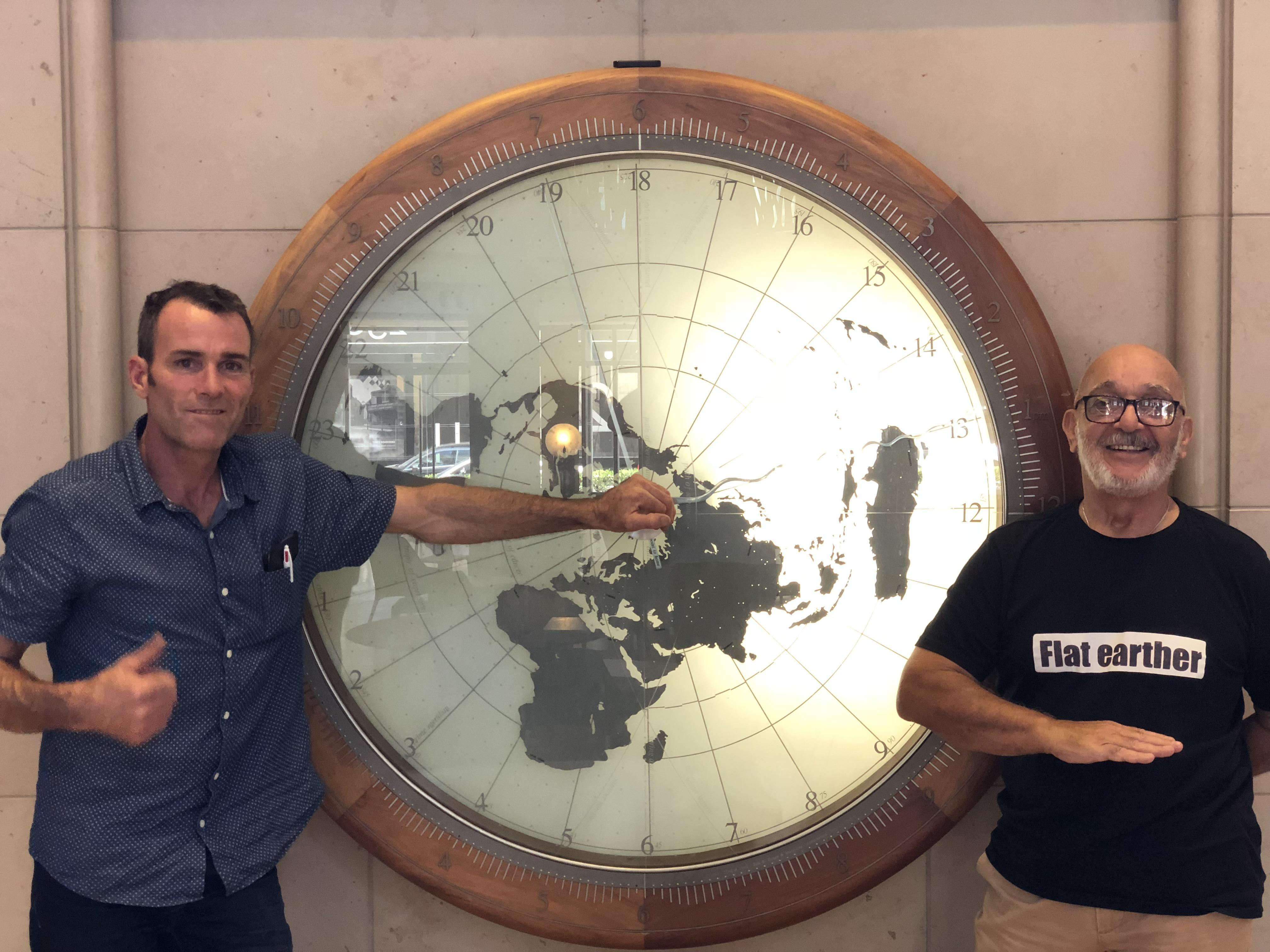 Lee and Artigas, the two people who turned up to the flat-Earth convention, in front of a map of the world.