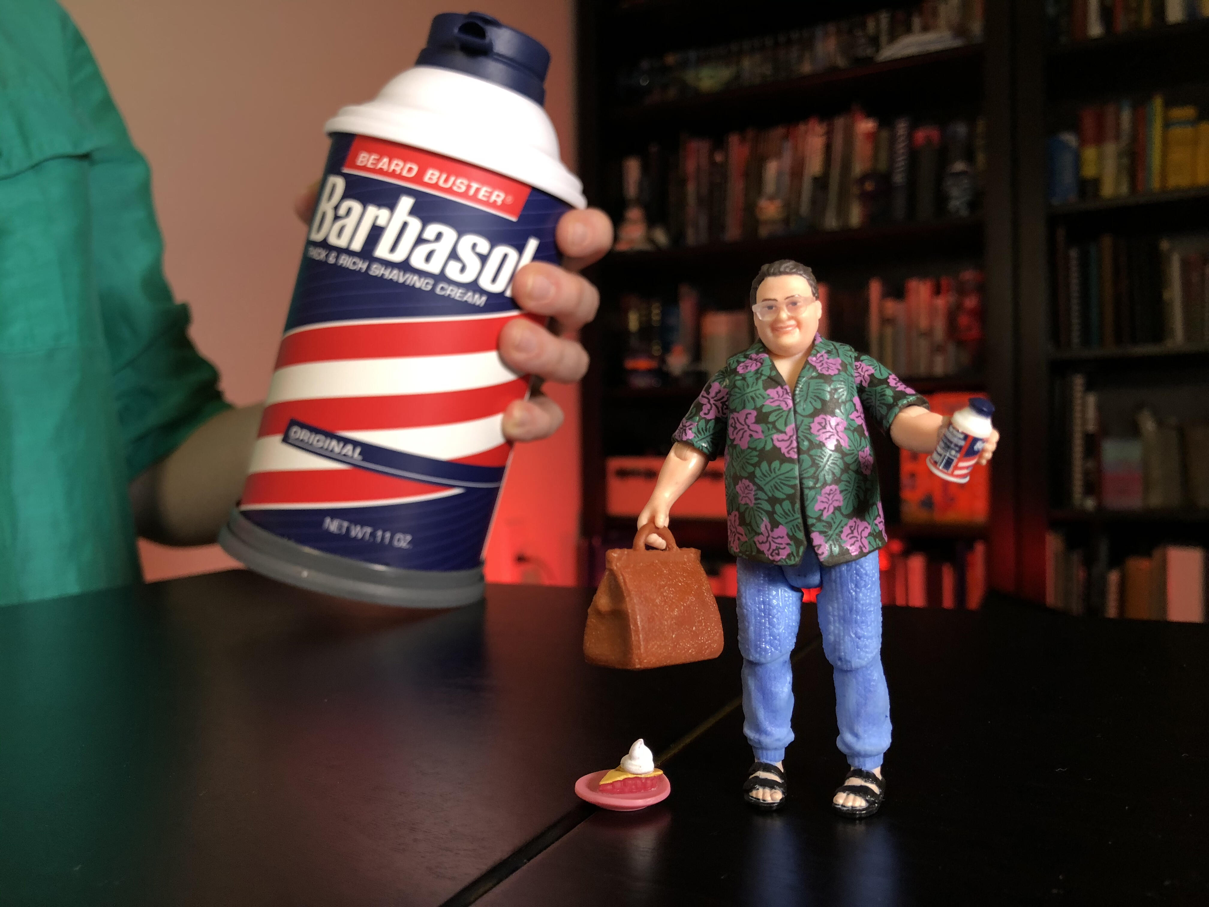 "<p>Mattel's Jurassic Park Dennis Nedry tucks away inside a Barbasol can with his bag of cash, ""shaving cream,"" and a ruined slice of pie.</p>"