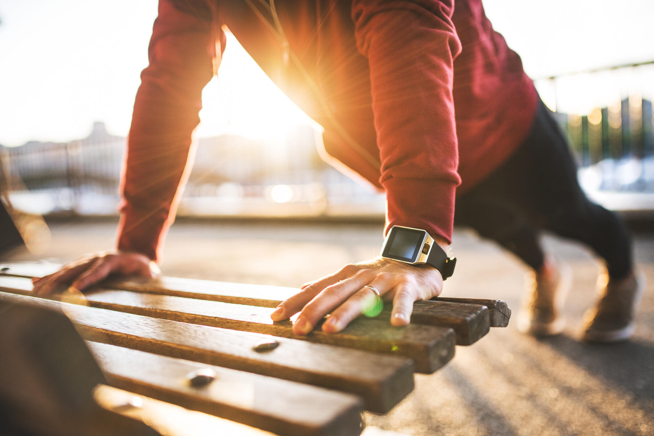 A man in a red shirt with a fitness watch on, doing push-ups on a park bench at sunset.