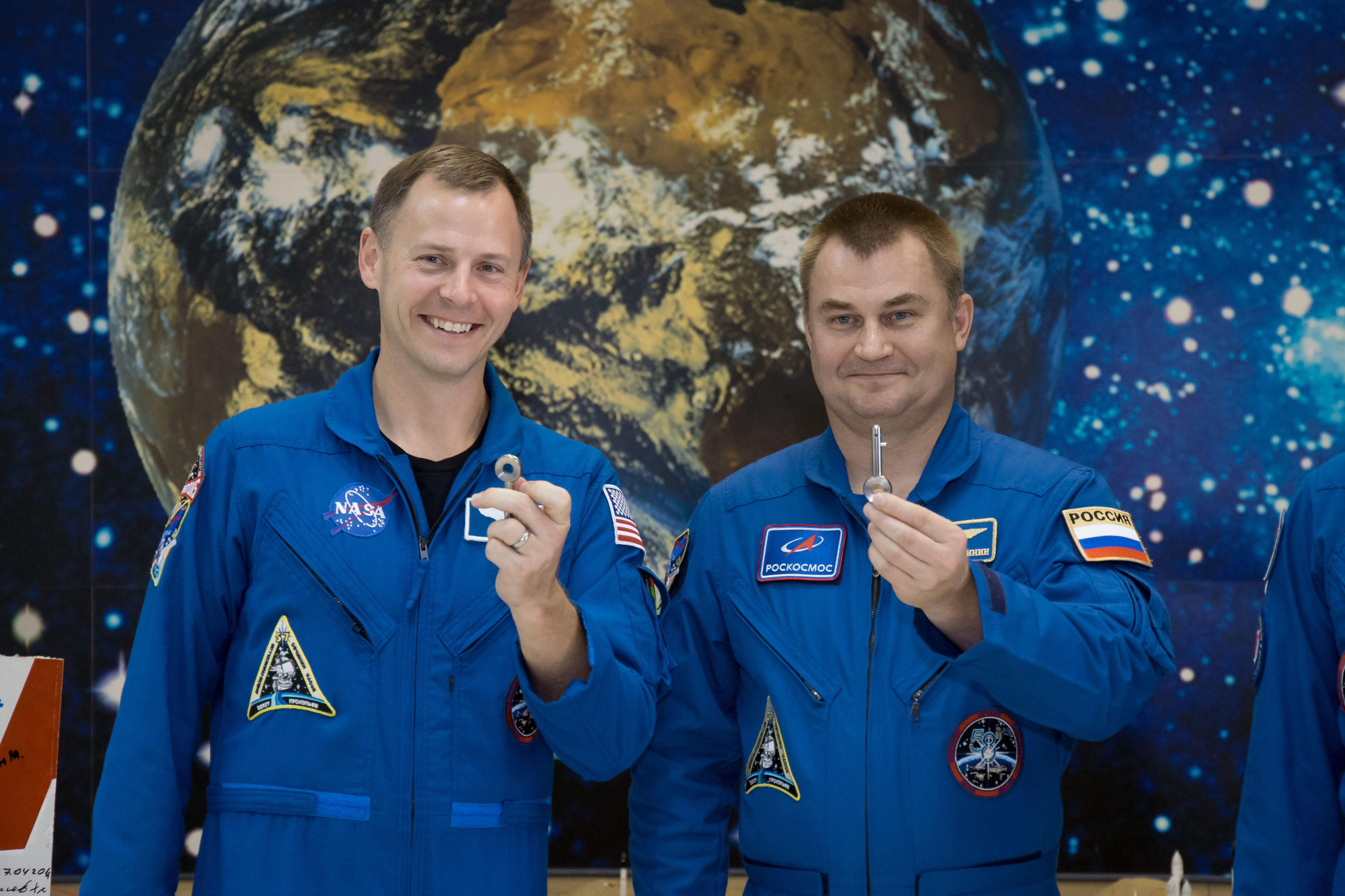 """At the Baikonur Cosmodrome Museum in Kazakhstan, Expedition 57 Nick Hague of NASA (left) and Alexey Ovchinin of Roscosmos (right) display """"launch keys"""" they were presented Oct. 6 during a traditional pre-launch tour of the facility. Hague and Ovchinin wil"""
