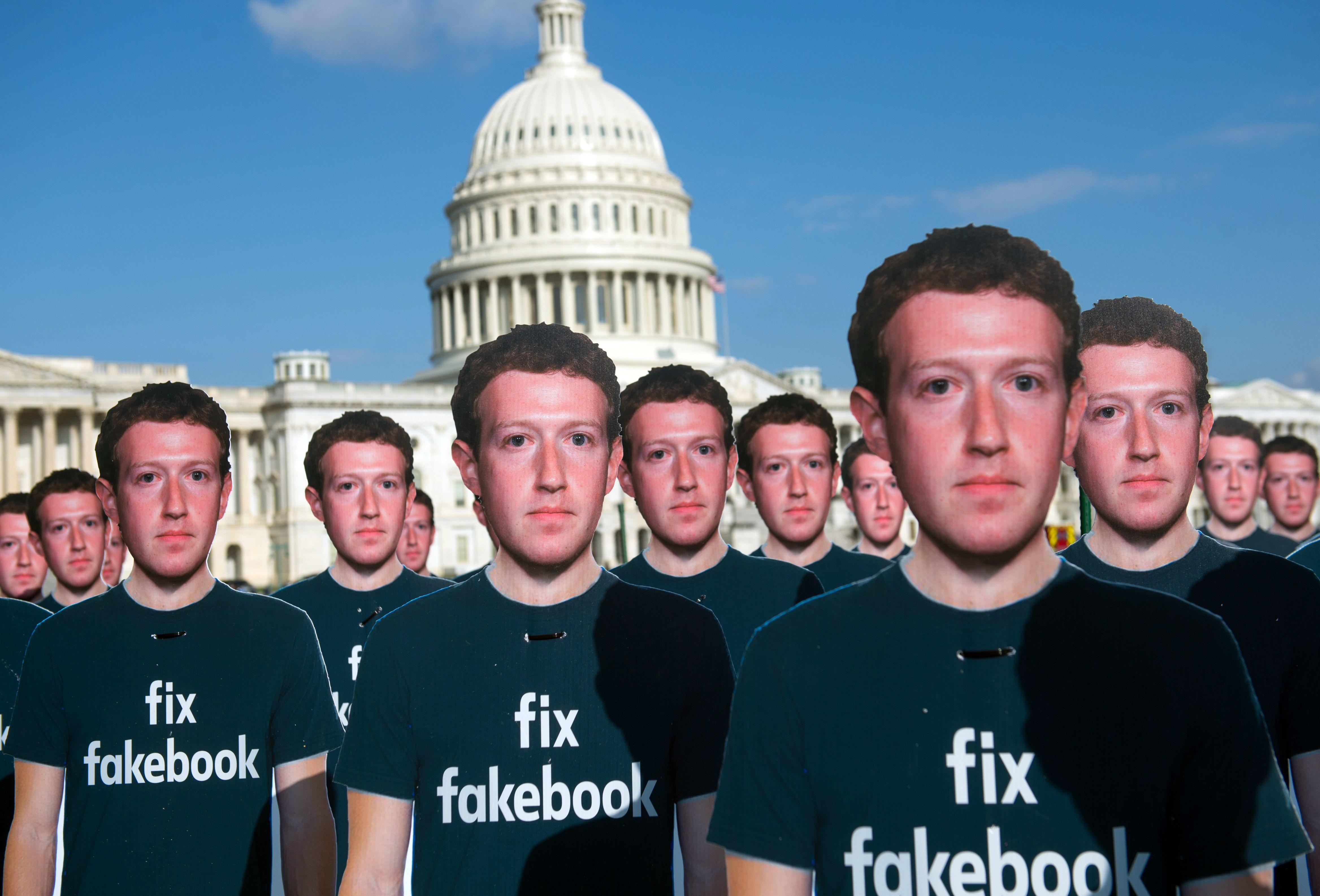 Cardboard cutouts of Mark Zuckerberg with the US Capitol building in the background.