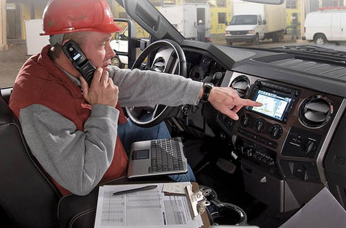 A construction worker using an in-dash computer in an F-Series truck.