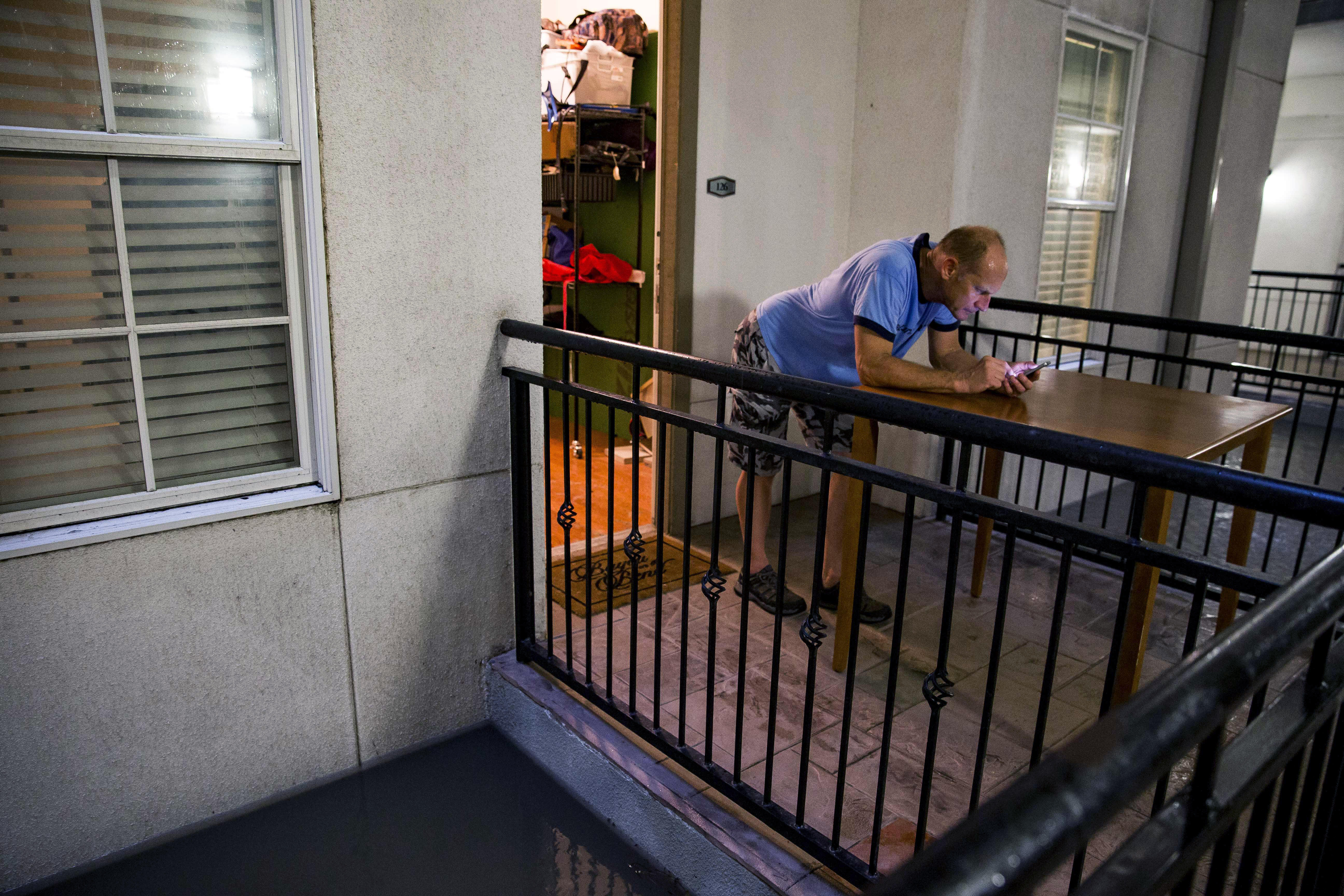 A Houston resident checks his phone as flood waters rise near his door.